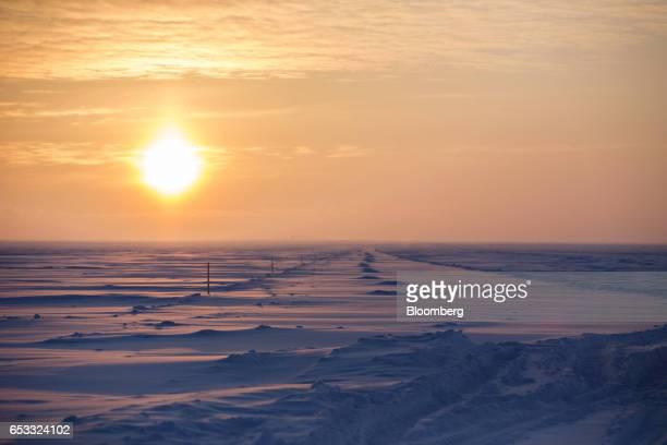 The sun rises over an ice road on the frozen Beaufort Sea near the Caelus Energy LLC Oooguruk Development Project in Harrison Bay Alaska US on Friday...