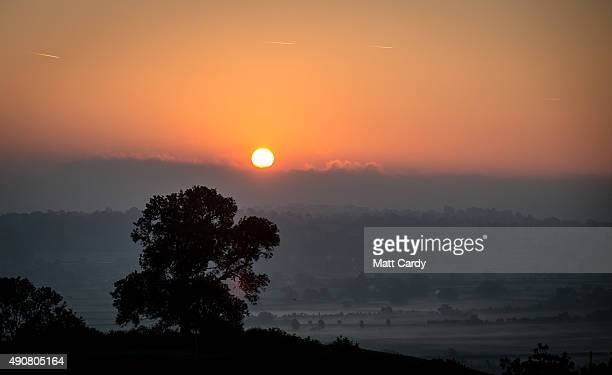 The sun rises over mist lingering in fields in Somerset on October 1 2015 in Glastonbury England The fine autumn weather that some parts of the UK...