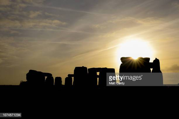 The sun rises over Stonehenge as people take part in a winter solstice ceremony at the ancient neolithic monument of Stonehenge near Amesbury on...