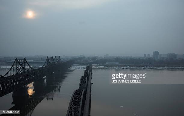 The sun rises over the banks of the Yalu River in the Chinese border town of Dandong opposite to the North Korean town of Sinuiju on February 8 2016...