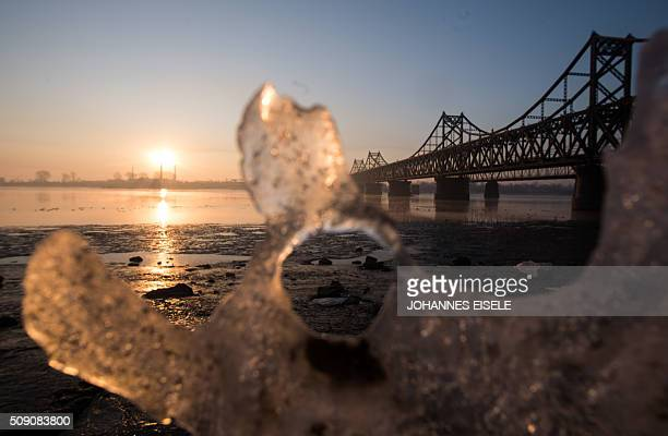 The sun rises over the bridge on the banks of the Yalu River in the Chinese border town of Dandong opposite to the North Korean town of Sinuiju on...