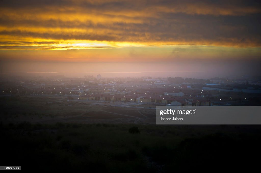 The sun rises over the city on November 24, 2012 in Villacanas, Spain. During the boom years, where in its peak Spain built some 800,000 houses a year accompanied by the manufacturing of millions of wooden doors where needed, the people of Villacanas were part of Spain's middle class enjoying high wages and permanent jobs. During the construction boom years the majority of the doors used within these new developments were made in this small industrial town. Approximately seven million doors a year were once assembled here and the factory employed a workforce of almost 5700 people, but the town is now left almost desolate with the Villacanas industrial park now empty and redundant. With Spain in the grip of recession and the housing bubble burst, Villacanas is typical of many former buoyant industrial Spanish towns now struggling with huge unemployment problems.