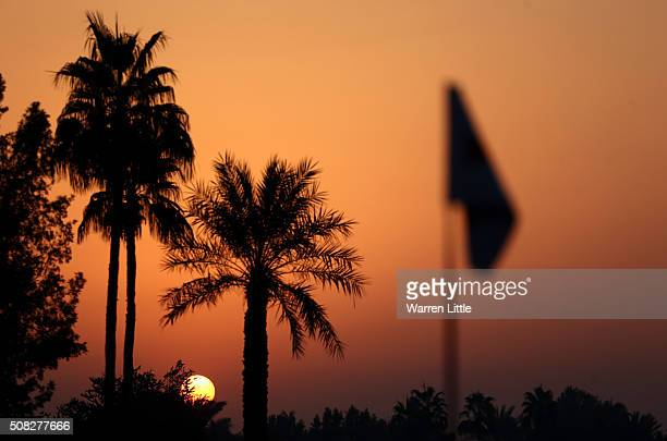 the sun rises over the course at the start of the first round of the Omega Dubai Desert Classic on the Majlis course at the Emirates Golf Club on...