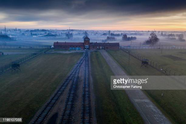 The sun rises over the early morning mist blanketing the barbed wire electrified fence and the Death Gate the Auschwitz II-Birkenau extermination...