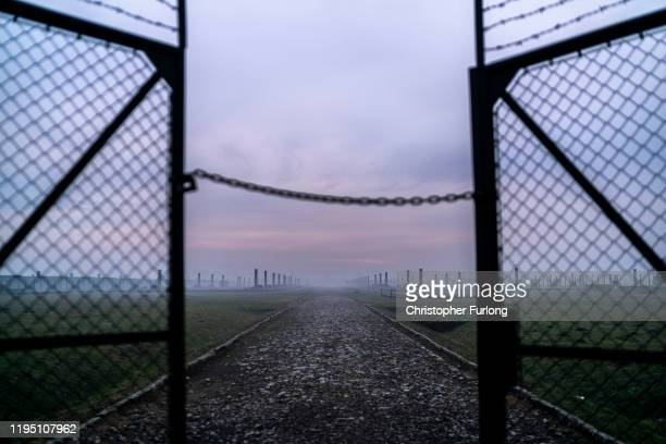 The sun rises over the early morning mist blanketing the barbed wire electrified fence that surrounds the Auschwitz II-Birkenau extermination camp on...