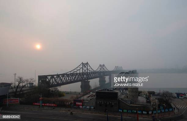 The sun rises over the Friendship bridge on the Yalu River connecting the North Korean town of Sinuiju and Dandong in Chinese border city of Dandong...