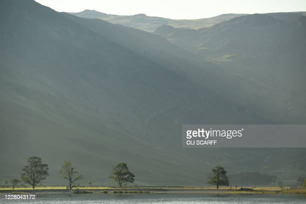 The sun rises over the hills above Buttermere Lake in the Lake District in north west England on August 14 as many people take advantage of the...