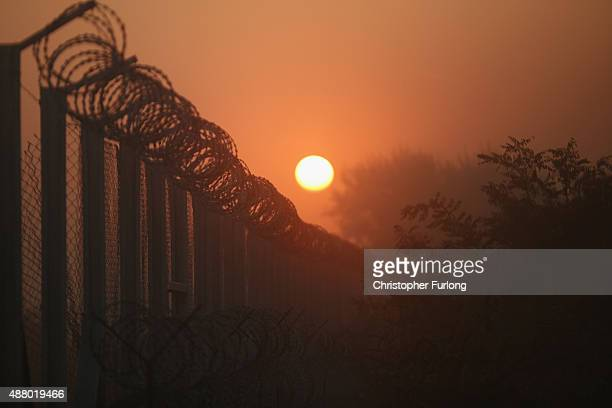 The sun rises over the nearly completed border fence at the Hungarian border with Serbia on September 13 2015 in Roszke Hungary A record number of...