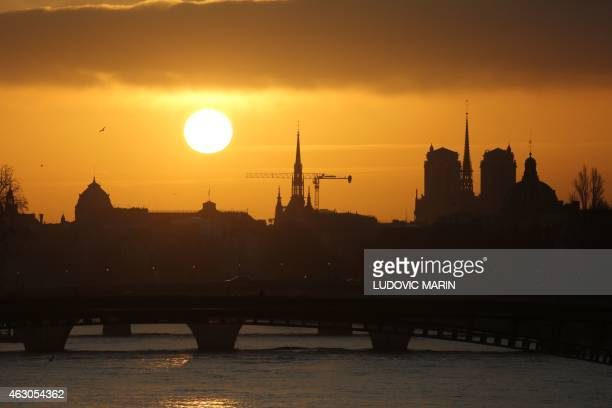 The sun rises over the river Seine the Sainte Chapelle and NotreDame cathedral on February 9 2015 in Paris AFP PHOTO / LUDOVIC MARIN