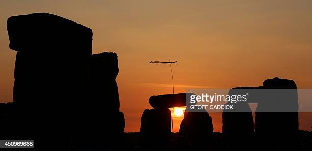 The sun rises over the standing stones at the prehistoric monument Stonehenge near Amesbury in Southern England on June 21 as revelers gather to...