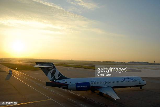 The sun rises over the tarmac at Hartsfield Jackson International Airport in Atlanta as an AirTran flight prepares for takeoff