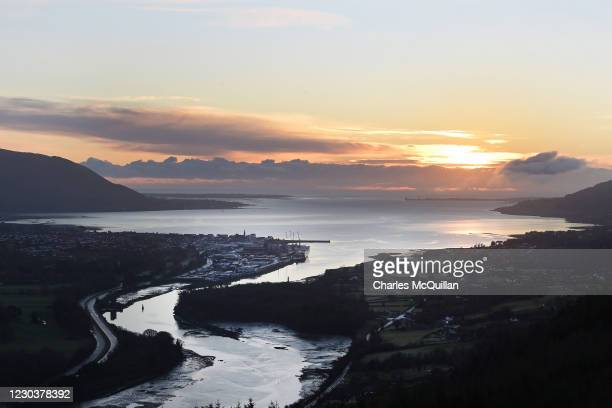 The sun rises over Warrenpoint harbour in the north and Carlingford in the south of Ireland which are separated by the Newry river on January 1, 2021...
