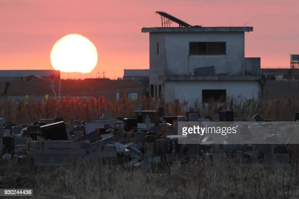 The sun rises past a cemetery and abandoned building in Namie Fukushima prefecture on the seventh anniversary of the Great East Japan earthquake on...