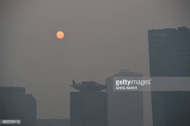 The sun rises through smog on the fourth day of a pollution red alert in Beijing on December 22, 2015. The Chinese capital imposed the highest tier...