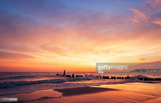 the sun rising at the beach in the morning - avondschemering stockfoto's en -beelden