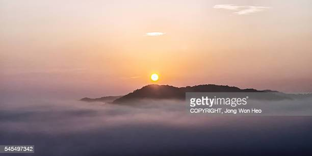 The sun rising over an sland on the sea of clouds