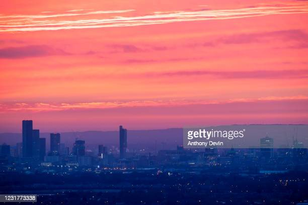 The sun sets above Manchester city centre on March 19, 2020 in Manchester, England.