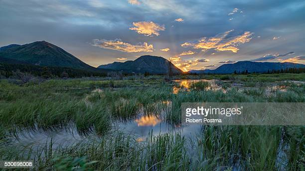 The sun sets and creates bands of light behind Toad Mountain near Annie Lake; Whitehorse, Yukon, Canada
