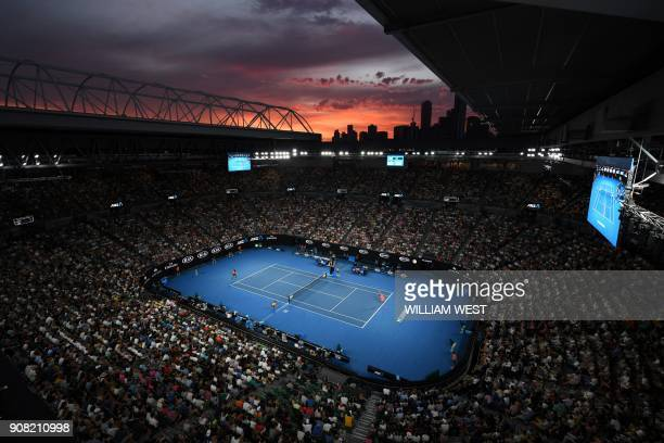TOPSHOT The sun sets as Australia's Nick Kyrgios plays against Bulgaria's Grigor Dimitrov in their men's singles fourth round match on day seven of...