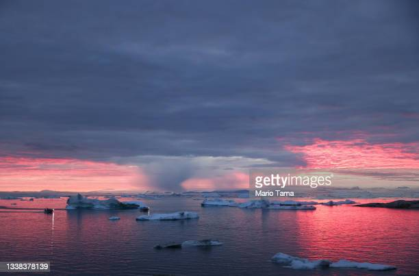 The sun sets as rain falls beyond floating ice and icebergs in Disko Bay above the Arctic Circle on September 04, 2021 in Ilulissat, Greenland. 2021...