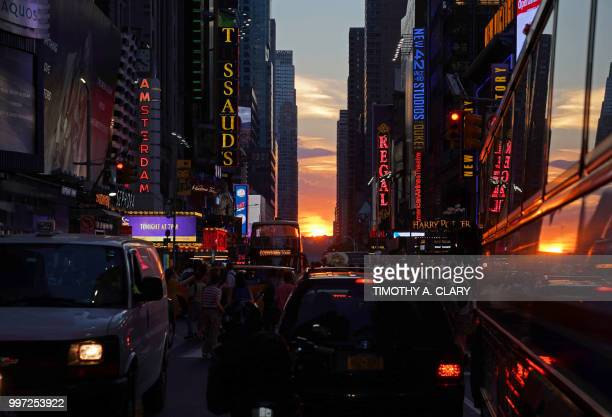The sun sets as seen from 42nd street in Times Square in New York City on July 12 2018 during Manhattanhenge Manhattanhenge sometimes also referred...