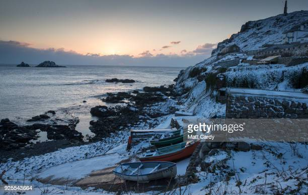 The sun sets as snow covers fishing boats left at Priest's Cove at Cape Cornwall near Penzance on February 28 2018 in Cornwall England Freezing...
