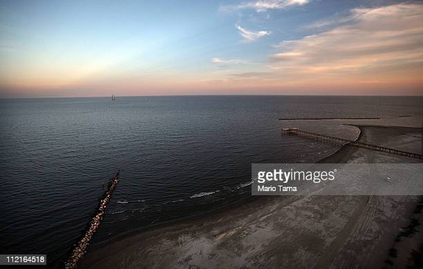 The sun sets as waves wash up from the Gulf of Mexico onto the beach April 13 2011 in Isla Grand Terre Louisiana Oil from the BP oil spill washed up...