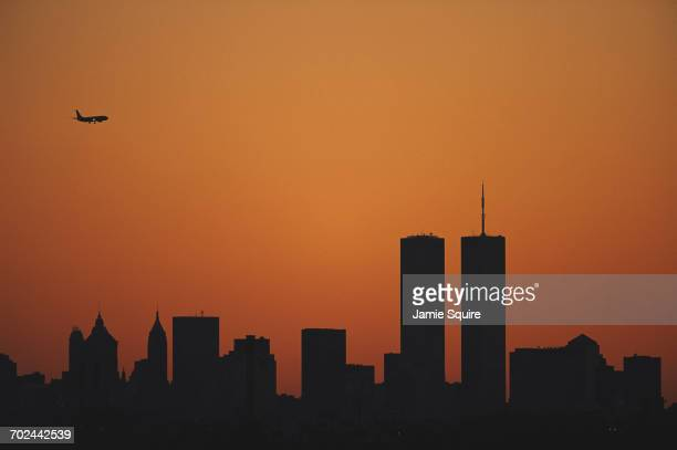 The sun sets at dusk over the Manhattan skyline silhouetting the Twin Towers of the World Trade Center as a passenger jet airliner crosses the sky...