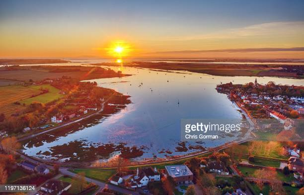 The sun sets at high tide on Bosham Harbour in West Sussex on December 3, 2019 in Bosham, United Kingdom. King Canute famously commanded the tide to...