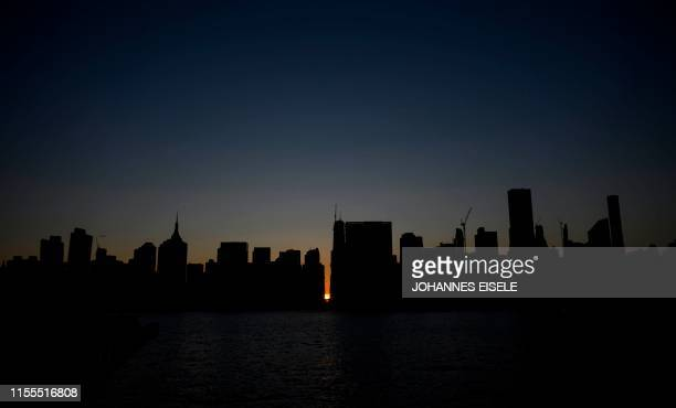 TOPSHOT The sun sets behind 42nd Street in Manhattan during a power outage in New York City on July 13 2019 Subway stations plunged into darkness and...