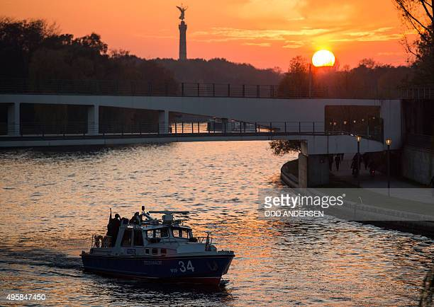 The sun sets behind a police boat patrolling the river Spree outside the Chancellery in Berlin on November 5 following a visit of the Tunisian Prime...
