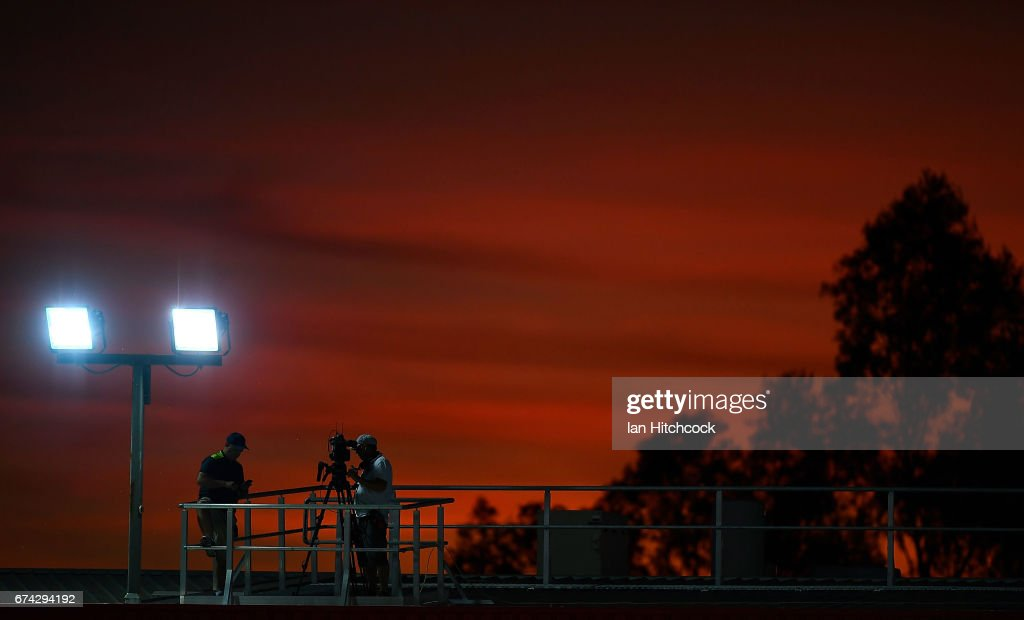 The sun sets behind a television cameraman on the western grandstand before the start of the round nine NRL match between the North Queensland Cowboys and the Parramatta Eels at 1300SMILES Stadium on April 28, 2017 in Townsville, Australia.
