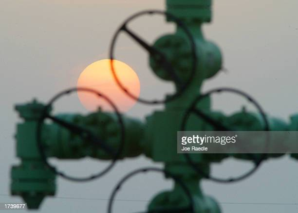The sun sets behind a wellhead of a Kuwait Oil Company oil well January 22 2003 on the northern border between Iraq and Kuwait in Kuwait Kuwait...