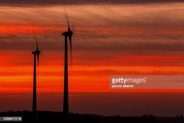 The sun sets behind a wind park near Renzow Germany 03 December 2015 The federal association 'WindEnergie' is advocating a more decentralised...
