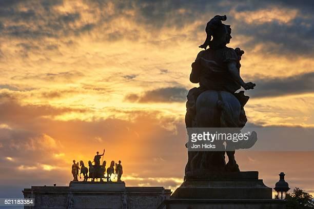The sun sets behind Arc de Triomph du Carrousel.