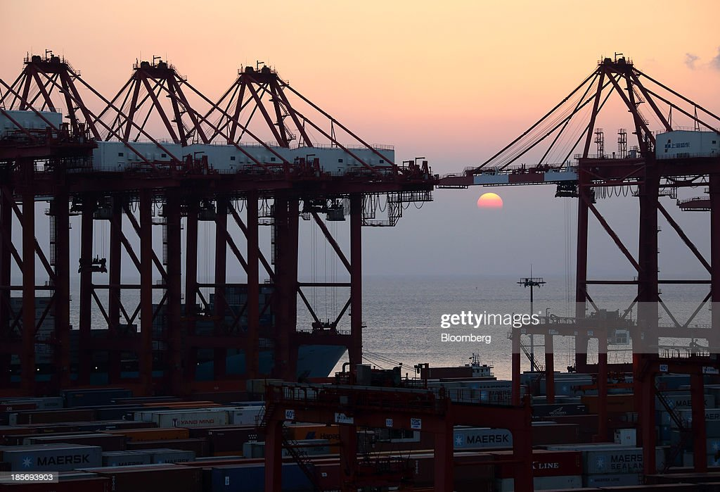 The sun sets behind cranes at the Yangshan Deep Water Port, part of China (Shanghai) Pilot Free Trade Zone's Yangshan free trade port area, in Shanghai, China, on Wednesday, Oct. 23, 2013. The area is a testing ground for free-market policies that Premier Li Keqiang has signaled he may later implement more broadly in the world's second-largest economy. Photographer: Tomohiro Ohsumi/Bloomberg via Getty Images