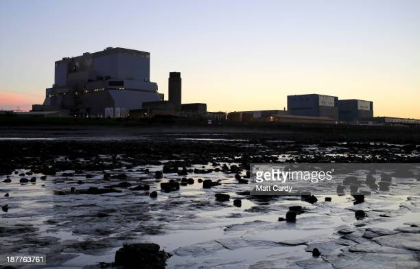 The sun sets behind Electricite de France SA's Hinkley Point B and Hinkley Point A nuclear power stations besides the Bristol Channel near Bridgwater...