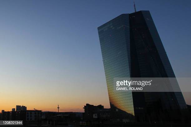 The sun sets behind European Central Bank ECB and the city skyline in Frankfurt, Germany, on March 24, 2019. - European stocks opened higher on...