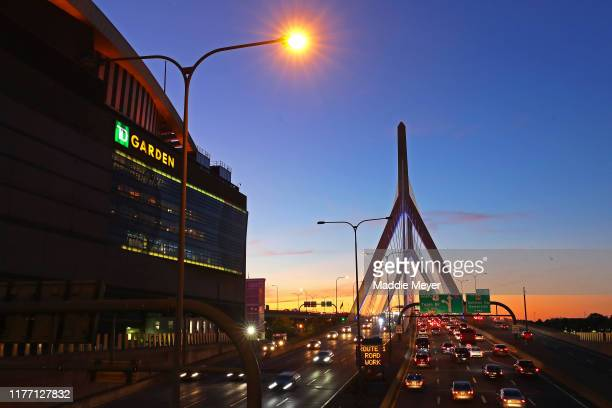 The sun sets behind TD Garden and the Leonard P Zakim Bunker Hill Memorial Bridge before the preseason game between the New Jersey Devils and the...