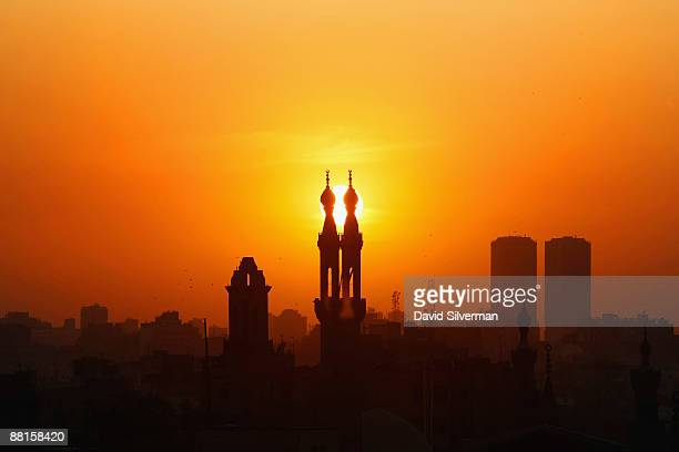 The sun sets behind modern buildings and mosque minarets on June 2 2009 in Cairo Egypt The Egyptian capital is preparing to receive US President...