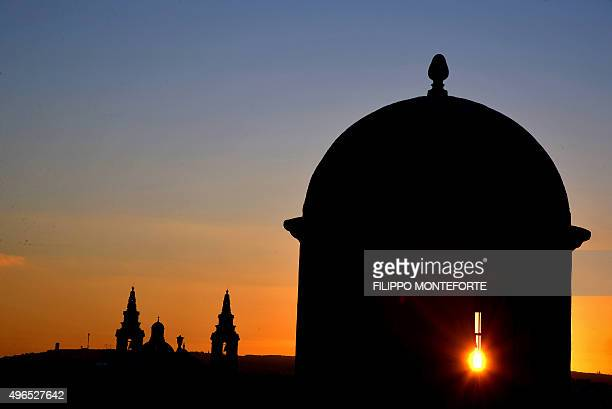 The sun sets behind monuments in La Valletta on November 10, 2015 on the eve of the European Union - Africa Summit on Migration to cope with the...