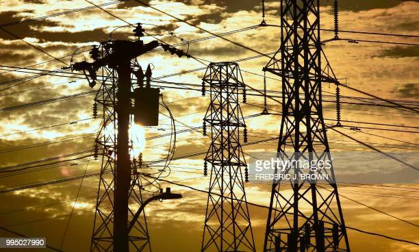 The sun sets behind power lines and poles in Rosemead California on July 9 2018 While temperatures have dropped slightly from the record heatwave...