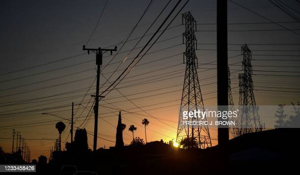 The sun sets behind power lines in Rosemead, California on June 14 amid an early season heatwave across much of California this week.