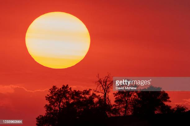 The sun sets behind smoke from a distant wildfire as drought conditions worsen on July 12, 2021 near Glennville, California. Authorities are bracing...