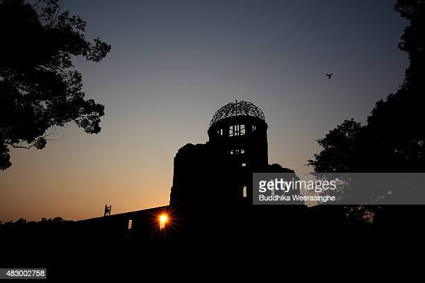 The sun sets behind the Atomic Bomb Dome at the Hiroshima Peace Memorial Park on the day before the 70th anniversary of the atomic bombing of...