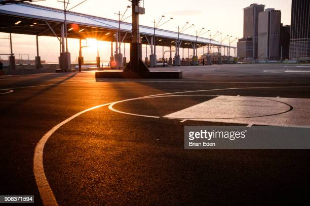 The sun sets behind the basketball courts at Pier Two in Brooklyn Bridge Park, New York