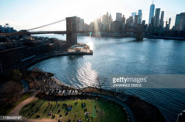 The sun sets behind the Brooklyn Bridge and the skyline of lower Manhattan on April 6 2019 in New York City