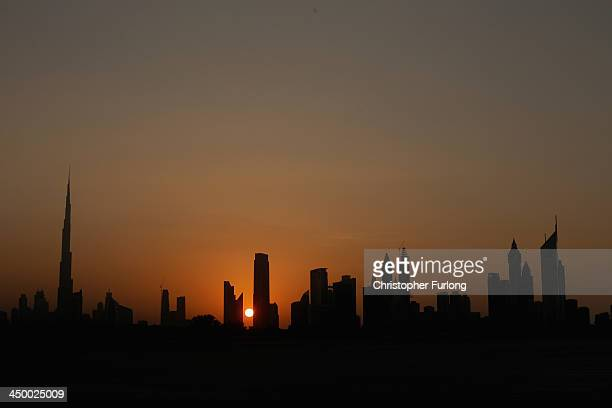 The sun sets behind the city skyline of Dubai on November 16 2013 in Dubai United Arab Emirates Dubai is recovering from its slump during the global...