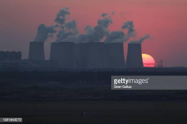 The sun sets behind the cooling towers of the Jaenschwalde coalfired power plant on October 11 2018 near Griessen Germany The Jaenschwalde power...