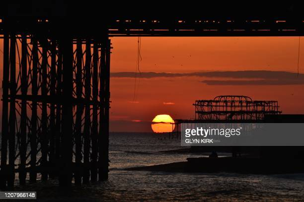 TOPSHOT The sun sets behind the derelict West Pier in Brighton on the south coast of England on March 22 2020 Up to 15 million vulnerable people in...